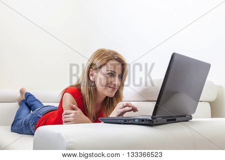 Woman using a laptop laying on the couch