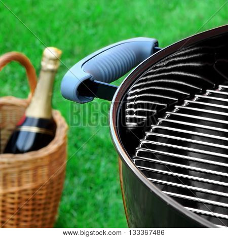 Barbecue Grill On The Lawn Close-up And Basket With Champagne