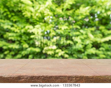 Stone board empty table in front of blurred background. Perspective brown stone over blur trees in forest - can be used for display or montage your mock up products. vintage filtered image.