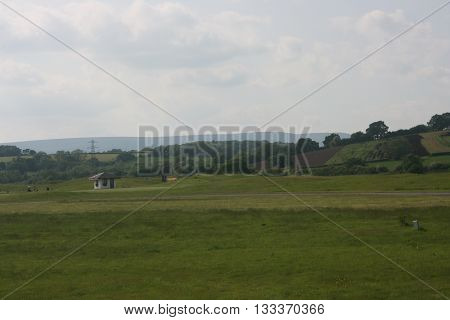 This photo shows the beauty of country side of Wales. Everything is breathtakingly beautiful. Green grass and trees. A cute little hut in the field.