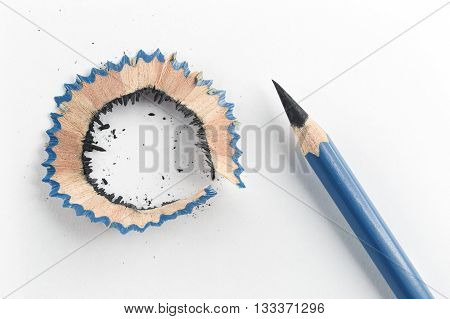 Close focus on sharp pencil and pencil shavings putting on white paper.