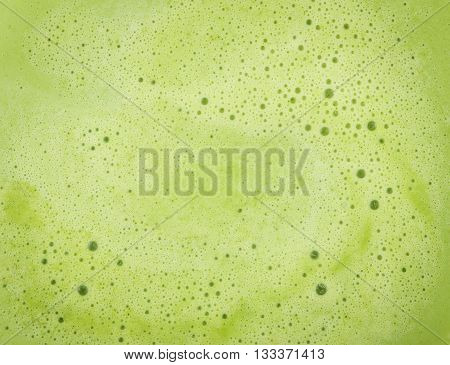 Background of close focus on melted green tea ice cream which having small air bubble floating on surface.