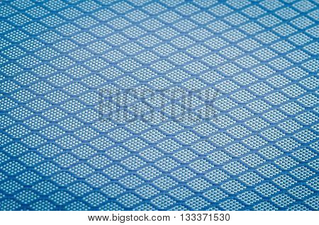 Background of close focus on dark blue texture fabric of polyester fiber and nylon. It designed as crossing pattern of crosswise rhombus which surround by vignette.