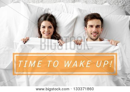 Text Time to wake up and young cute couple lying together in bed.