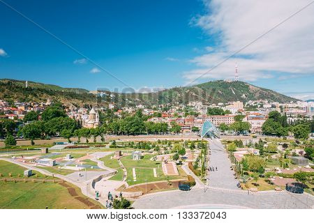 Scenic View Of Park Rike In Tbilisi, Georgia. In Background Is Visible Sioni Church, Pedestrian Bridge Of Peace Over The Kura River, Mount Mtatsminda.