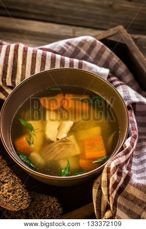 Bowl with fish soup and napkin on wooden table. Style rustic.