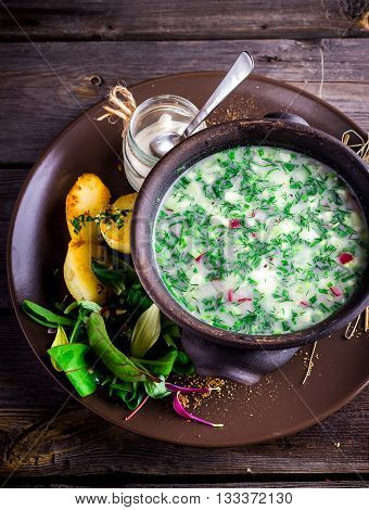 Traditional Russian kvass soup with vegetables - okroshka in a bowl on wooden table. Style rustic.