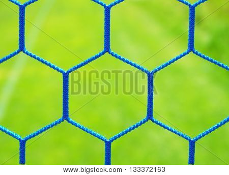 Detail of yellow blue crossed soccer nets, soccer football in goal net with grass on playground in background. Honeycomb shape.