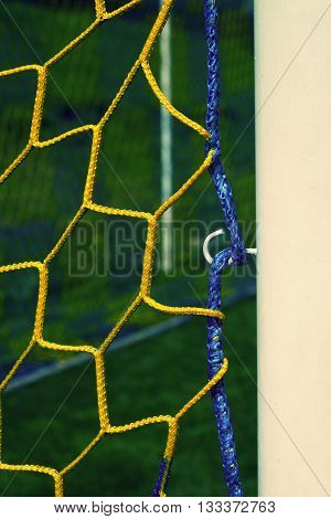 Hang Bended Blue Yellow Soccer Nets, Soccer Football Net. Plastic Grass And White Painted Line On Fo