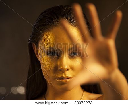 Portrait of beautiful woman with golden makeup and bodyart and outstretched forward arm. Focus on the face.