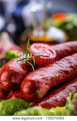 Sausage. Chorizo sausage. Raw smoked sausage with vegetable decoration.Lettuce salad herb rosemary tomato garlic olive oil.
