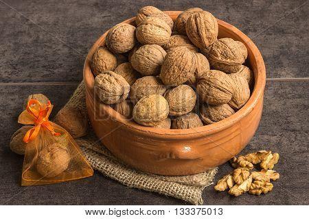 Walnuts in a ceramic pot on a dark background