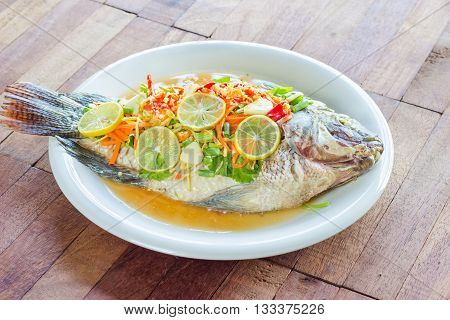 steamed Nilotica fishthai style steamed fish in spicy saucewood background