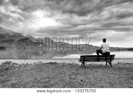 Wooden Bench For Relaxing On Shore. View On Alps Mountains With White Peaks Mirror