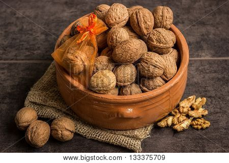 Walnuts in a ceramic bowl and a small gift on dark background