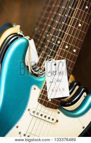 Used guitars at a instrument shop. Electric guitars on a guitar display stand with sale tag. Blue electric guitar in front.