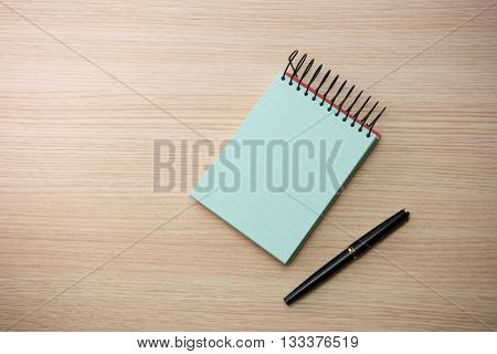 Blue paper memo pad with pen on wooden table or desk.