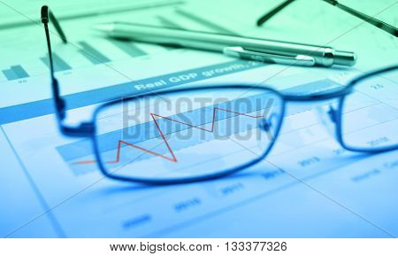 Glasses and pen on blue financial chart and graph success concept blue and green tone