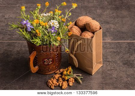 Walnuts in a paper bag next to a bouquet of wild flowers on a dark background