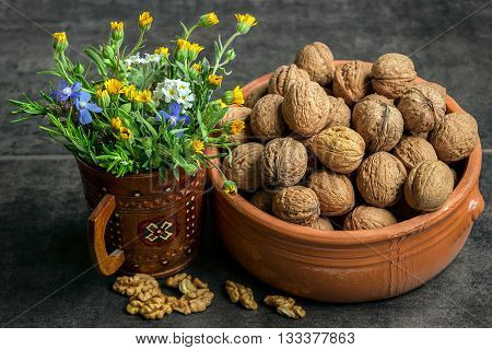 Walnuts in a ceramic pot on a dark background with a bouquet of wildflowers