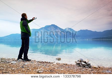 Tall Man Hold Cellphone, Take Photo Of Autumn Mountain Lake Scenery