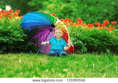 Kid, baby with rainbow umbrella in park. A child on a background of flowers. Summer scene in nature. Fun holidays. Childhood