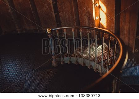 Old and rusty spiral stairs inside dark and spooky room