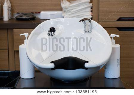 White washbasins for hairdresser at modern barbershop.