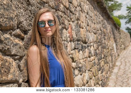 Modest young girl on the background of the old stone wall with dor