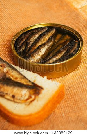 Open Can And Sandwich With Of Sprats On Sackcloth Background