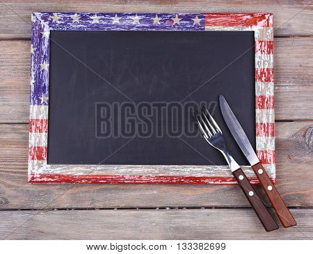 Blackboard blank on rustic wooden planks background. American cuisine food concept