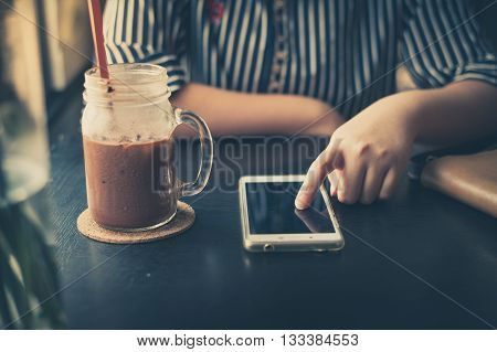 Young woman touching on smartphone screen with her left hand beside iced chocolate glass at cafe in afternoon time on weekend with vintage filter effect