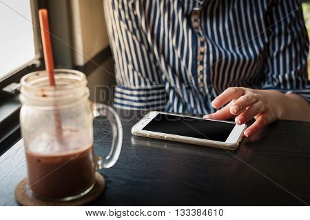 Young woman using smartphone on wood table beside iced chocolate glass at cafe in afternoon time on weekend
