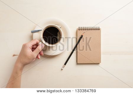 Young hipster male left hand holding coffee cup on wood table beside small notebook with blank area on brown cover in morning time