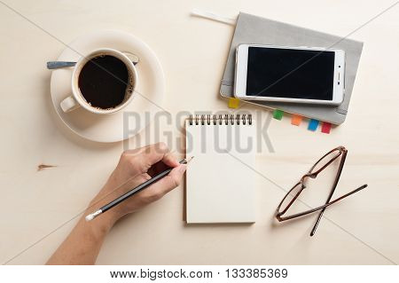 Young man left hand writing on blank notebook on wood table with coffee cup smartphone and glasses beside in morning time