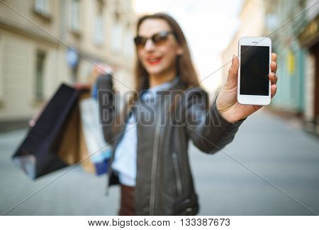 Online shopping concept - beautiful woman with shopping bags and smart phone in the hands on a street