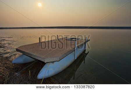 Lake in Canada at sunrise with a pontoon boat on shore