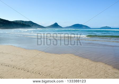 Pristine beach with blue water and the tide approaching