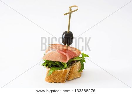 Thin slices spanish serrano ham skewer with olive and lettuce isolated on white background
