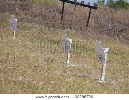 Three steel silhouettes used for firearm practice with plates behind