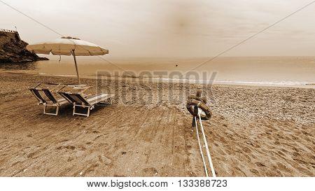 Beach Umbrella and Lifebuoy on the Sandy Coast at Sunrise Vintage Style Sepia