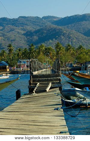 Jetty improvisation Riung harbour with boats, Flores Indonesia