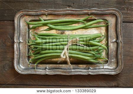 Fresh green french beans on a metal tray on wooden background