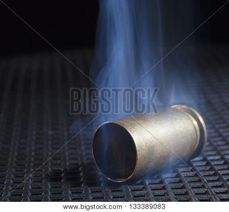 Handgun brass with smoke on a black grate