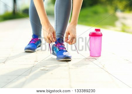 Running shoes - woman tying shoe laces. Closeup of female sport fitness runner getting ready for jogging outdoors in summer