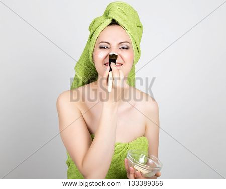 beautiful Young woman dressed in a bath towel makes a cosmetic mask on the face. beauty industry and home skin care concept.