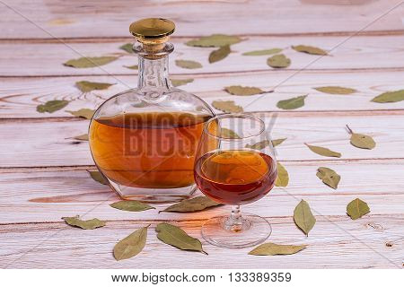 Cognac bottle and glass on the wooden table with leaves - normal view