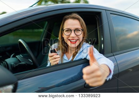 Young happy woman sitting in a car with the keys in her hand and thumb up - concept of buying a used car or a rental car
