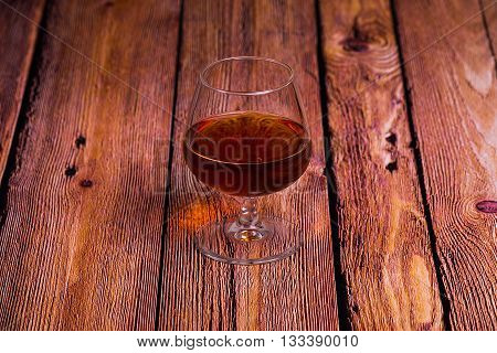 Cognac glass on the red old wooden table - close up photo