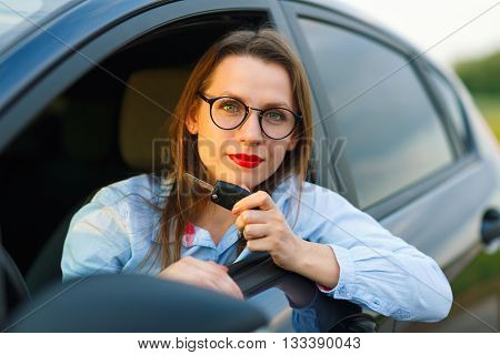 Young pretty woman sitting in a car with the keys in hand - concept of buying a used car or a rental car